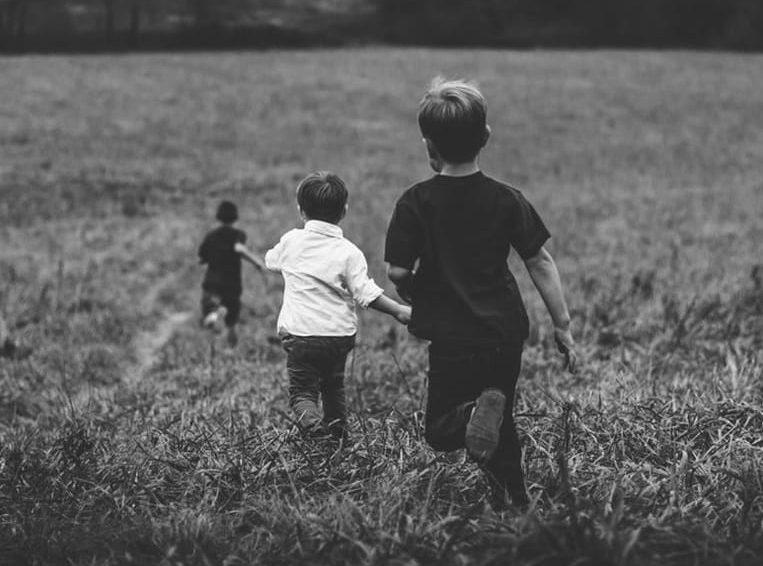 bambini corrono felici all'aperto in mezzo alla natura