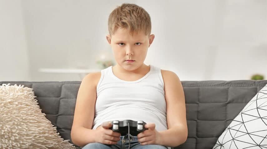 bambino sedentario mentre gioca videogiochi